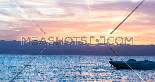 A small boat docked in the sea by the sunrise in the background