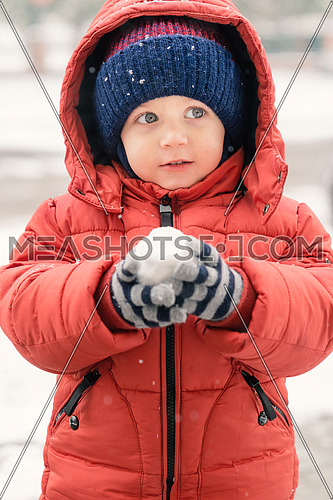 Beautiful infant boy while it is snowing looks towards the void, holding a snowball in his hands, covered with a red winter jacket and a woolen hat, close-up.