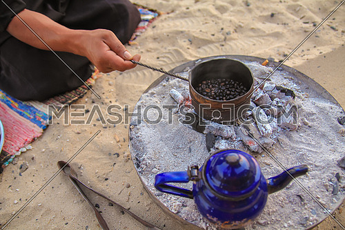 Roasting traditional Gabana Coffee and a kettle of tea on charcoal in the desert