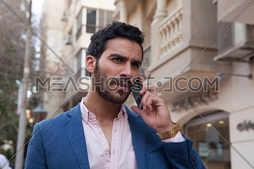 A young business man talking on the phone in the street