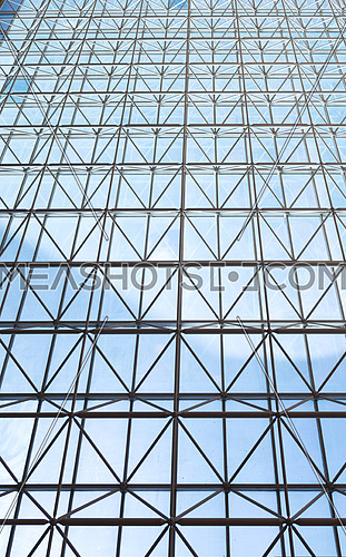 Contemporary steel structure and transparent glass roof revealing blue sky with light clouds