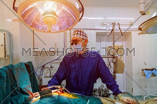 Surgery doctor in surgery center for interventions with surgery tools in surgeon operation microsurgery doing invasive surgery for open heart