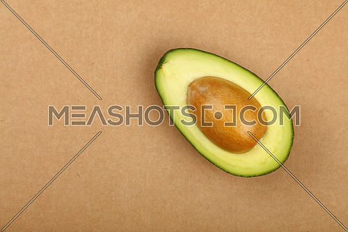 One fresh ripe green avocado half with pit stone on natural brown kraft paper background, detail, close up, elevated top view, elevated top view