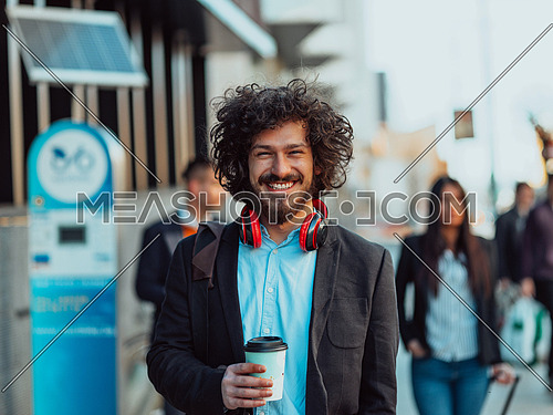 Happy student with afro haircut walking on campus while wearing his manbag and his headphones.