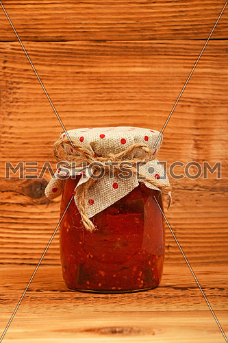 One glass jar of homemade pickled pepper, paprika and eggplant salad with dotted textile top decoration at brown vintage wooden surface