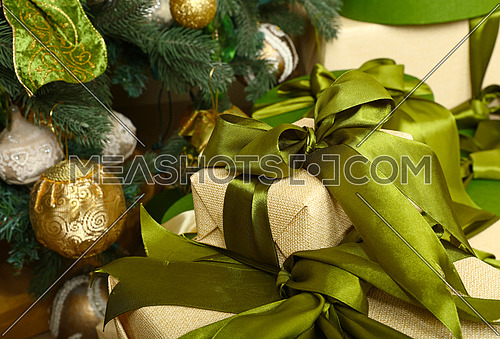 Close up green and beige paper wrapped gift boxes with ribbon bows under decorated Christmas tree, high angle front view