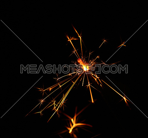 Close up one firework sparkler over black background with defocused blue bokeh, low angle side view