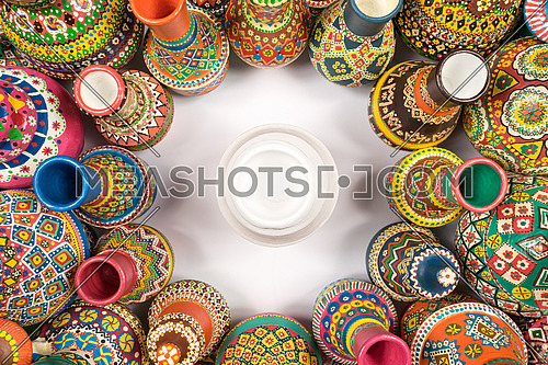 Top view showing a composition of artistic colorful painted handcrafted pottery vases compacted in a circle around a single white vase on white background