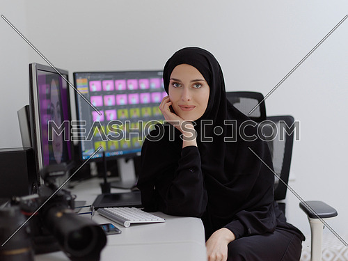 Portrait of young muslim female graphic designer. Hijab girl with the two monitors in background showing her work. Technology concept