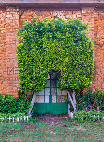 Orange colored bricks stone wall with grunge green metal grid door covered with arched tree, green grass, and plants at summer time, Montaza Public park, Alexandria, Egypt