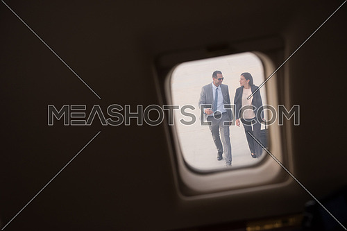 Young middle eastern successful businessman and businesswoman walking towards private jet
