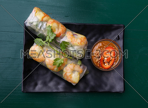 Close up portion of two fresh spring rolls with shrimps and dipping chili sauce on plate over table, elevated top view, directly above