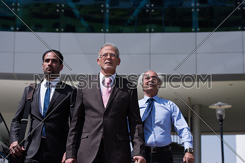 A group of business executives walking in front of a corporate building