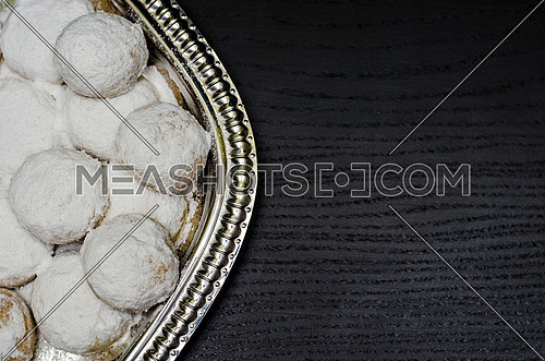Kahk seted up on a silver plate ready to get served on a black wooden background table