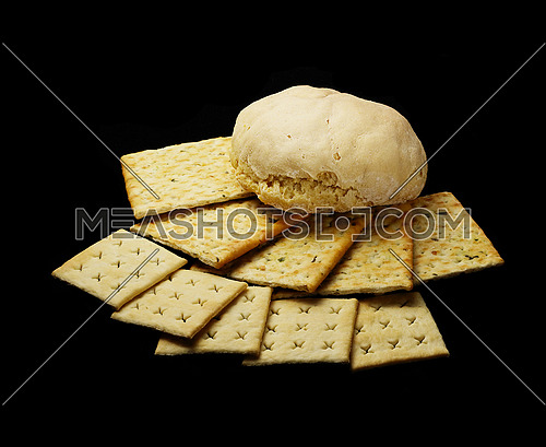fresh bread and crackers on black background