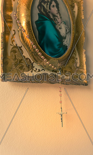 Hung on a painting an old rosary with crucifix on a light background,copy space.used split toning for vintage/old style.