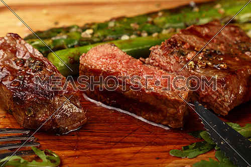 Cut slices of grilled juicy medium cooked beefsteak served on wooden board with fresh green rocket salad, fork and knife, close up, high angle view