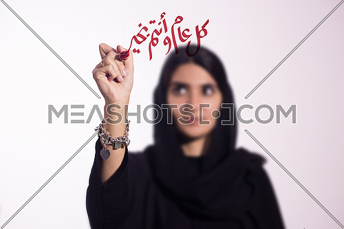 """Arabian middle eastern business woman writing with a marker on virtual screen in arabic كل عام و انتم بخير suggesting season greeting """"happy new year"""" """"Happy Birthday"""" isolated on white background"""