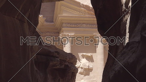 Left pan reveal of the Treasury in canyon mouth of Petra