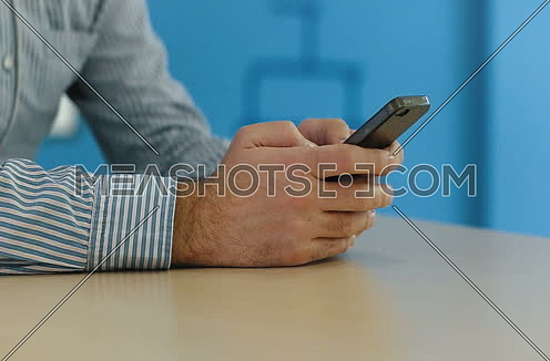 Shot of hands using cell phone in startup office