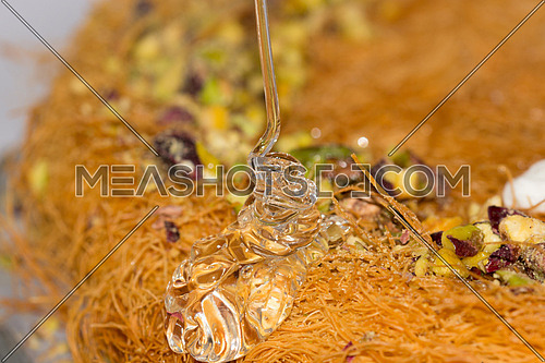 a close up on a kunafa tray with honey being poured