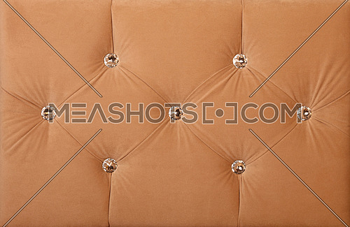 Close up background of pastel beige color soft velvet bed headboard with rhinestone crystals, front view