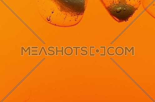 Clear ice cubes with air bubbles float rotating and melt down in cold iced black tea or whiskey, extreme close up, low angle side view, slow motion