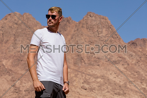 Long shot for a male tourist exploring Sinai Mountain for wadi Freij at day.