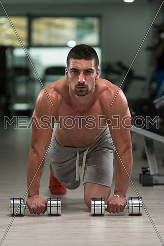 Young Athlete Doing Pushups With Dumbbells As Part Of Bodybuilding Training