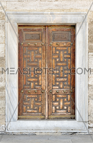 Wooden aged engraved door and exterior stone wall, Sultan Ahmet Mosque, Istanbul, Turkey