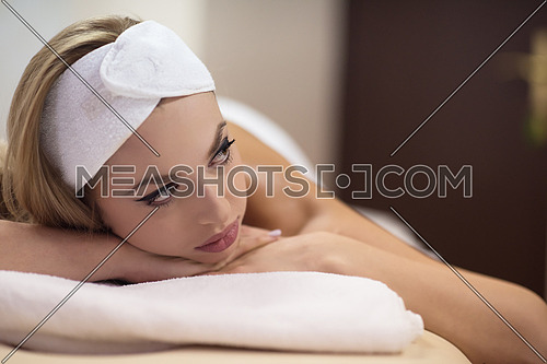 Relaxed young beautiful  woman laying on massage table