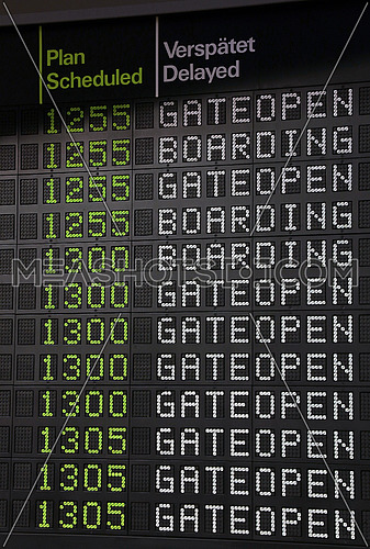 Flight information panel desk at airport, with time, boarding and gate open messages, close up, low angle view