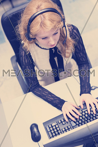 top view of a young smiling female call centre operator doing her job with a headset