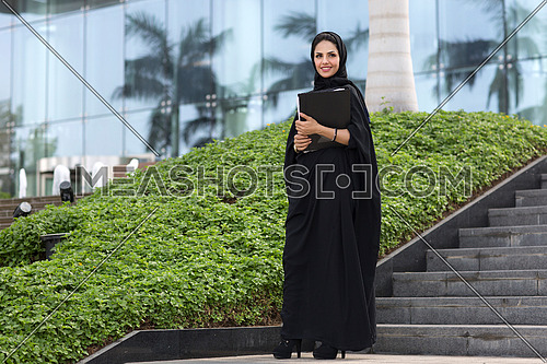 Saudi lady standing and holding a holder, wearing black abaya in front of glass building and a small garden in background at day.