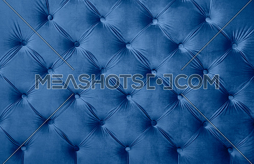 Blue velvet capitone textile background, classic retro Chesterfield style checkered soft tufted fabric furniture diamond pattern decoration with buttons, close up