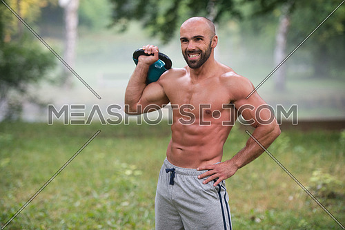 Strong And Muscular Young Fitness Man -  Holds Up A Green Kettlebell Outdoors  - Sports And Fitness - Concept Of Healthy Lifestyle - Fitness Male