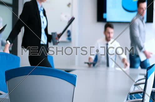 Business People entering Meeting Around Table In  Modern Office