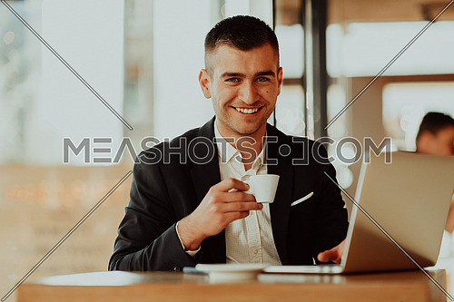 businessman sitting at the cafeteria with a laptop and smartphone. Businessman texting on smartphone while sitting in a pub restaurant. Businessman working and checking email on the computer.