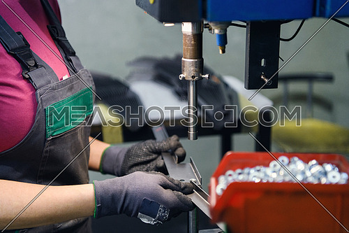 woman wearing a face mask due to coronavirus pandemic while working in the modern metal industry and using a drill. High quality photo