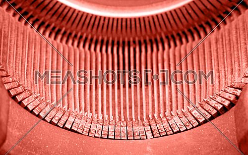 Close up coral pink color toned old vintage antique retro typewriter with Latin typeface, high angle view