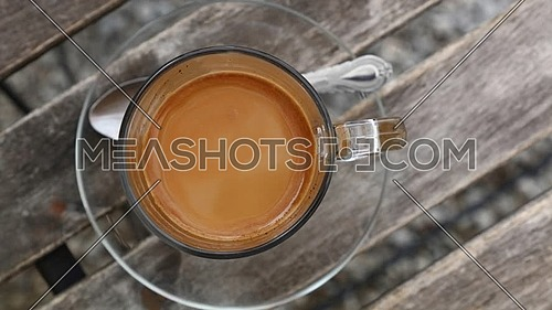 Close up one glass cup full of coffee with milk, spoon and saucer on wooden table with slow motion animated cinemagraph spin of coffee froth, elevated