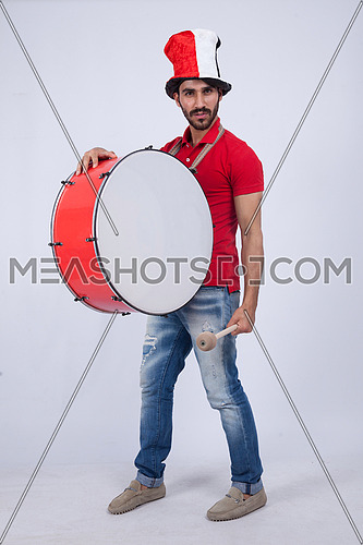 A young man holding big drums cheering on a white background