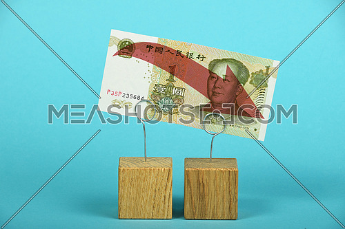 China economy crisis, decline of Chinese yuan, one yuan banknote with red arrow down at wooden metal holders over blue
