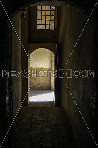 a photo from inside a historical house in old Fatimid Cairo , Egypt showing an abstract concept , light coming from the door ,walls