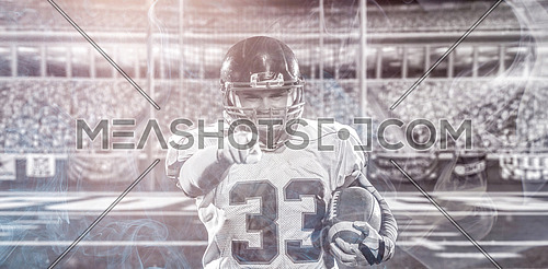 portrait of confident American football player holding ball while standing on big modern stadium field with lights and flares at night
