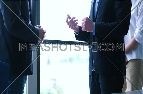 Portrait smiling businessman shaking hands with clients at end of meeting