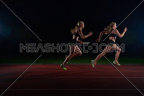 woman athletic runners passing baton in relay race