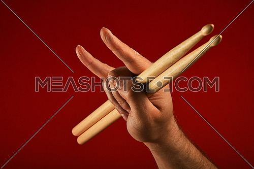Man hand holding two drumsticks with devil horns rock metal gesture sign over red background, side view