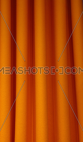 Heavy orange color pleated felt textile curtain background with portiere drape folds, side view close up
