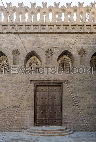 Aged wooden weathered door, perforated arched stucco window decorated with floral patterns, and three steps on stone bricks wall, Ibn Tulun Mosque, Cairo, Egypt